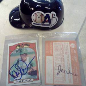 Baseball cards signed by Dave Duncan and Joe Torre, along with a plastic souvenir mini-helmet given away at the show.