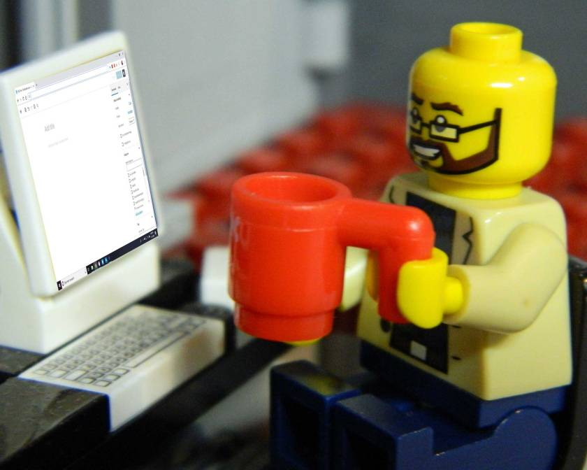 A Lego minifigure drinking tea in front of a computer